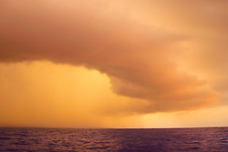 Pouring rain from massive storm clouds over Kailua Kona at sunset, Big Island, Hawaii, Pacific Ocean