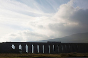 A train crossing Ribblehead Viaduct or Batty Moss Viaduct carries the Settle-Carlisle Railway across valley of the River Ribble at Ribblehead, in North Yorkshire Dales, England, UK. This impressive Victorian architectural wonder was designed by engineer, John Sydney Crossley and was built between 1870 and 1874.