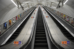 © Licensed to London News Pictures. 20/03/2020. London, UK. 11pm the escalators at Leicester Square,  on what would usually be one of the busiest nights of the week. London's underground network that at its peak handles 5 million passenger journeys a day was left all but abandoned on Friday as the coronavirus outbreak escalated. This latest phase of social distancing follows as the government announced the immediate closure of bars, pubs and restaurants to reduce person to person contact and virus transmission. Photo credit: Guilhem Baker/LNP