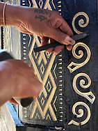 A local man carves intricate patterns into wood, Tana Toraja Regency, South Sulawesi, Indonesia, Southeast Asia