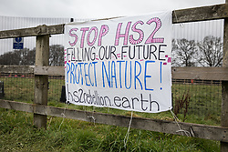 Great Missenden, UK. 18th March, 2021. A banner calling for the scrapping of the HS2 high-speed rail link project is pictured in front of works to fell a row of hundred-year-old oak trees in Leather Lane. Almost 40,000 people have recently signed a petition calling for the trees lining the ancient country lane not to be felled to make way for a temporary haul road and construction compound and local residents and conservationists have accused HS2 contractors of destroying active bird boxes on the site.