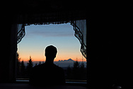 A young man watches the sunset as Mt Iliamna stands in the distance.