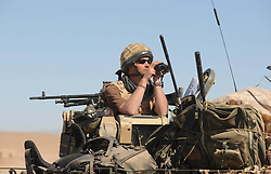 Prince Harry looks through binoculars from his position on the turret of his Spartan armoured vehicle in the desert in Helmand Province, Southern Afghanistan on February 18, 2008.