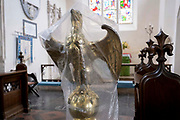 The lectern in the form of an eagle is covered by plastic between religious services in St Marys, a rural English church in Baconsthorpe, on 28th June 2021, in Baconsthorpe, Norfolk, England. The eagle was believed to be the bird that flew highest in the sky and was therefore closest to heaven.