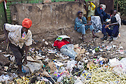 A group a young men and boys sniff glue and hang out in a rubbish site in central Thika, Kenya.