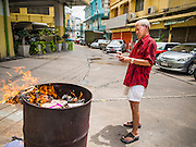 """10 AUGUST 2014 - BANGKOK, THAILAND: A man steps back after dropping a pile of """"Hell Money"""" into a burn barrel in Bangkok for Ghost Month. Hell money is a form of joss paper printed to resemble legal tender bank notes and is used in religious ceremonies in Chinese communities. The seventh month of the Chinese Lunar calendar is called """"Ghost Month"""" during which ghosts and spirits, including those of the deceased ancestors, come out from the lower realm. It is common for Chinese people to make merit during the month by burning """"hell money"""" and presenting food to the ghosts.    PHOTO BY JACK KURTZ"""