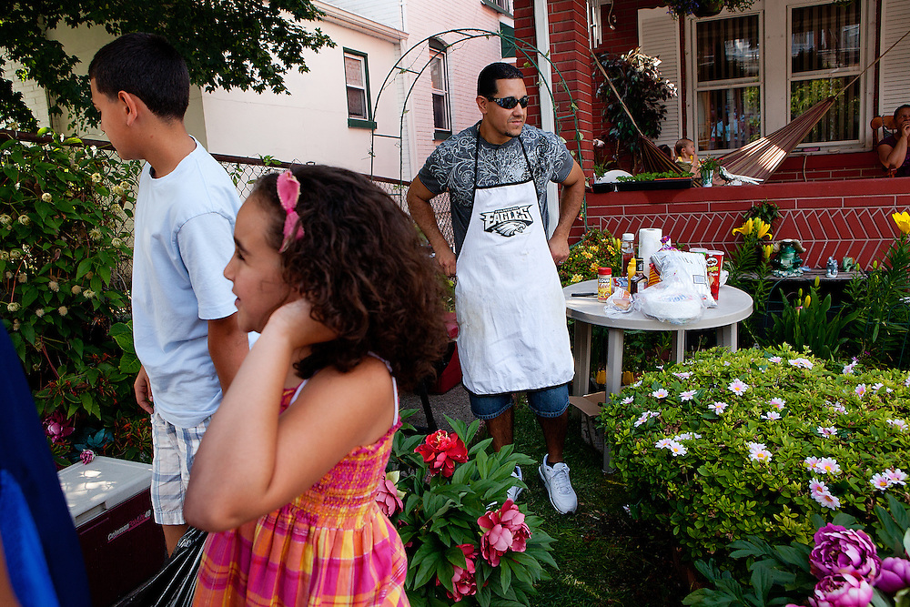BETHLEHEM, PA – JUNE 19, 2011: Tony Figueroa, 37, dons a Philadelphia Eagles apron in preparation for a Father's Day barbecue in South Bethlehem with his children, Jayden and Kylie. Figueroa has family ties to Puerto Rico but grew up in the Lehigh Valley. He teaches English as a second language in Broughal Middle School in Bethlehem.<br /> <br /> As the population of second and third generation Hispanics increases dramatically in the United States, a new boldness can be sensed among Latinos in America, stretching far beyond the southern border states. Demographers in Pennsylvania say the towns of Bethlehem, Allentown and Reading are set to become majority-minority cities, where Hispanics comprise a bigger portion of the population than whites. As this minority population increases dramatically in the region, Latinos are inching closer to their own realization of the American Dream, while gradually shifting the physical and cultural landscapes of their communities.