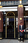 "Doorman at Cartier. Exclusive shops on New Bond Street, Mayfair, central London. It is one of the principal streets in the West End shopping district and is more upmarket. It has been a fashionable shopping street since the 18th century. Technically ""Bond Street"" does not exist: The southern section is known as Old Bond Street, and the northern section, which is rather more than half the total length, is known as New Bond Street. The rich and wealthy shop here mostly for high end fashion and jewellery."