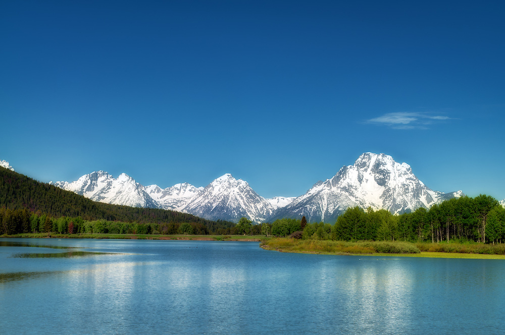 Beautiful snowy mountains, a crystal-blue lake and a gorgeous summer day in the Grand Teton National Park, in northwestern Wyoming.