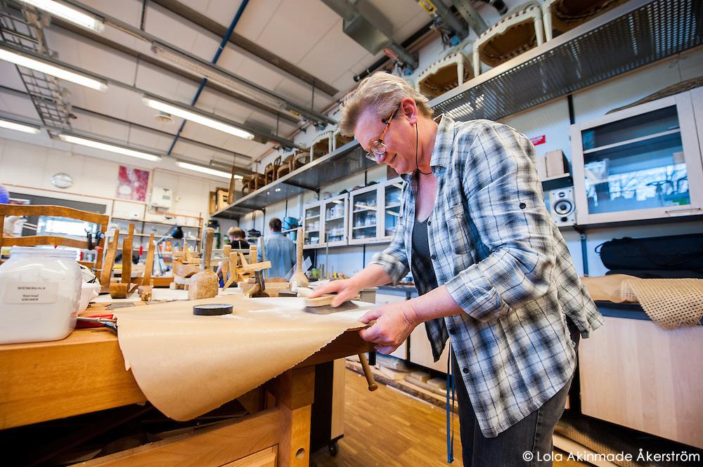 Furniture conservation professor Charlotta Ekholm polishing interior parts for furniture.
