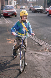 Young girl riding bike wearing reflective band and safety helmet,
