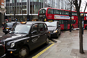 With engines running, traditional black cabs queue for fares, consequently blocking bus traffic outside the Selfridge's department store on Oxford Street, on 4th March 2019, in London England.