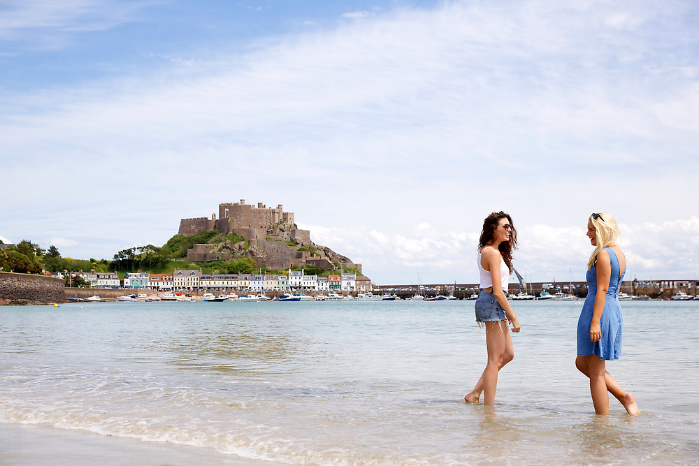 Girls socialising in the sea on the beach in Grouville, with Mont Orgueil Castle and Gorey harbour in the background