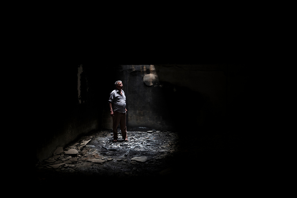 Naem Nuh Baqtar stands in the basement of his family's burned-out home in the predominately Christian town of Qaraqosh, which was occupied by ISIS for two years beginning in August 2014. Residents returned after its liberation to widescale damage and destruction.  (May 5, 2017)