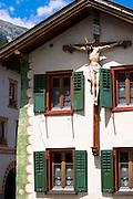 Christian crucifix on a traditional house in Mustair, Switzerlan