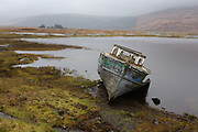 Beached fishing boat on shore at Pennyghael, Isle of Mull, Scotland. Pennyghael is a small community on the shores of Loch Scridain, and the boat sits rotting in the harsh northern winters after a lifetime of fishing in the seas off western Scotland. Loch Scridain is a long sea loch, with a west-south west aspect, on the western, or Atlantic coastline of the island of Mull.
