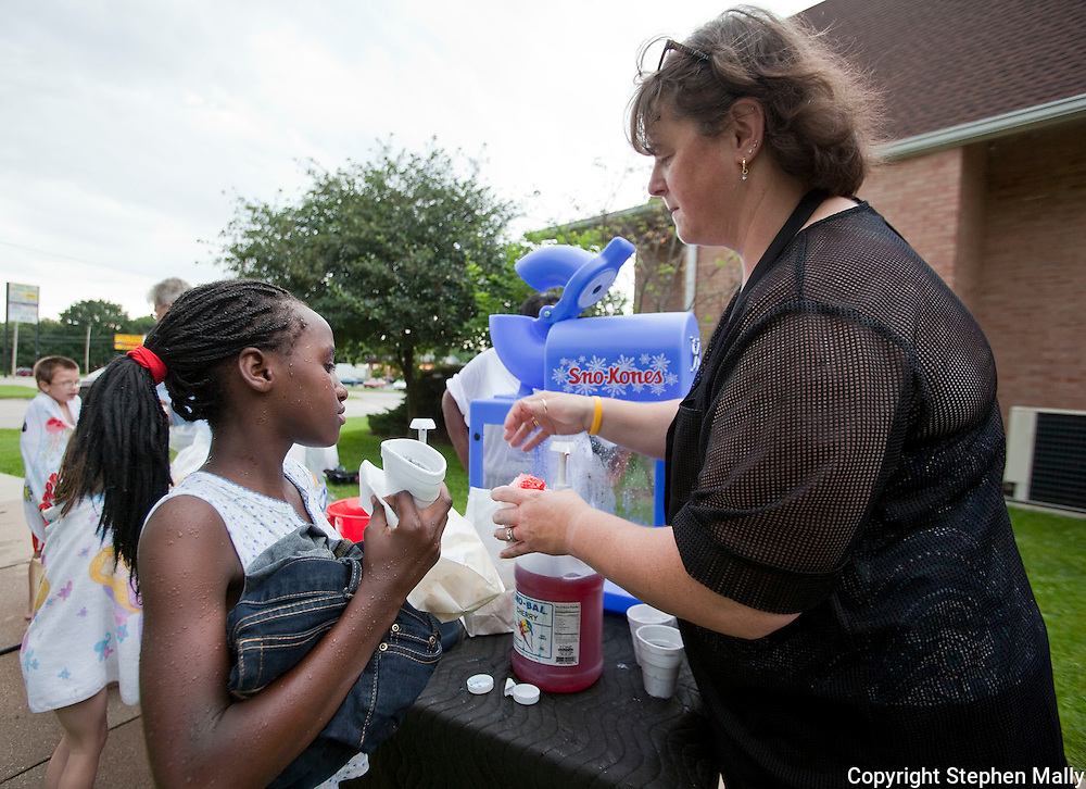 Diana Habimana (from left), 11, of Cedar Rapids waits for her snow cone from Lisa Cooley of Cedar Rapids during a Fun Friday at St. Mark's United Methodist Church at 4700 Johnson Ave. NW in Cedar Rapids on Friday, June 18, 2010.