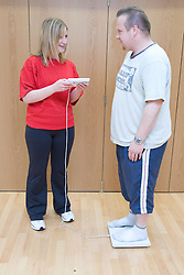 Fitness instructor performing a body MOT on a member at his sports leisure centre,