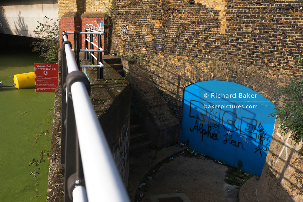 Stratford Olympic Park construction barrier marks boundary of no access to land near River Lea in East London.