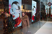 Shoppers merge with the image of a woman's face modelling sunglasses in Covent Garden in central London, on 4th December 2017, in London England.