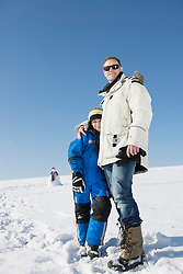 Father and son standing on snow, smiling, Bavaria, Germany