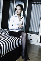beautiful caucasian woman in bedroom sitting on the bed hand massaging
