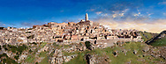 """Panoramic long view across """"la Gravina"""" ravine to the Sassi of Matera at sunrise, Basilicata, Italy. A UNESCO World Heritage site.<br /> <br /> The area of Matera has been occupied since the Palaeolithic (10th millennium BC) making it one of the oldest continually inhabited settlements in the world. <br /> The town of Matera was founded by the Roman Lucius Caecilius Metellus in 251 BC and remained a Roman town until  was conquered by the Lombards In AD 664 becoming part of the Duchy of Benevento.  Matera was subject to the power struggles of southern Italy coming under the rule of the Byzantine Roman, the Germans and finally Matera was ruled by the Normans from 1043 until the Aragonese took possession in the 15th century. <br /> <br /> At the ancient heart of Matera are cave dwellings known as Sassi. As the fortunes of Matera failed the sassy became slum dwelling and the appalling living conditions became be the disgrace of Italy. From the 1970's families were forcibly removed from the Sassi and rehoused in the new town of Matera. Today tourism has regenerated Matera and the sassi have been modernised and are lived in again making them probably the longest inhabited houses in the world dating back 9000 years. .<br /> <br /> Visit our ROMAN ART & HISTORIC SITES PHOTO COLLECTIONS for more photos to download or buy as wall art prints https://funkystock.photoshelter.com/gallery-collection/The-Romans-Art-Artefacts-Antiquities-Historic-Sites-Pictures-Images/C0000r2uLJJo9_s0<br /> .<br /> <br /> Visit our MEDIEVAL PHOTO COLLECTIONS for more   photos  to download or buy as prints https://funkystock.photoshelter.com/gallery-collection/Medieval-Middle-Ages-Historic-Places-Arcaeological-Sites-Pictures-Images-of/C0000B5ZA54_WD0s"""