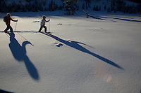 Russell Laman (age 12) and Jessica Laman (age 9)  cross-country skiing below the Teton Range, casting long shadows in the afternoon light.<br />Grand Teton National Park, Wyoming