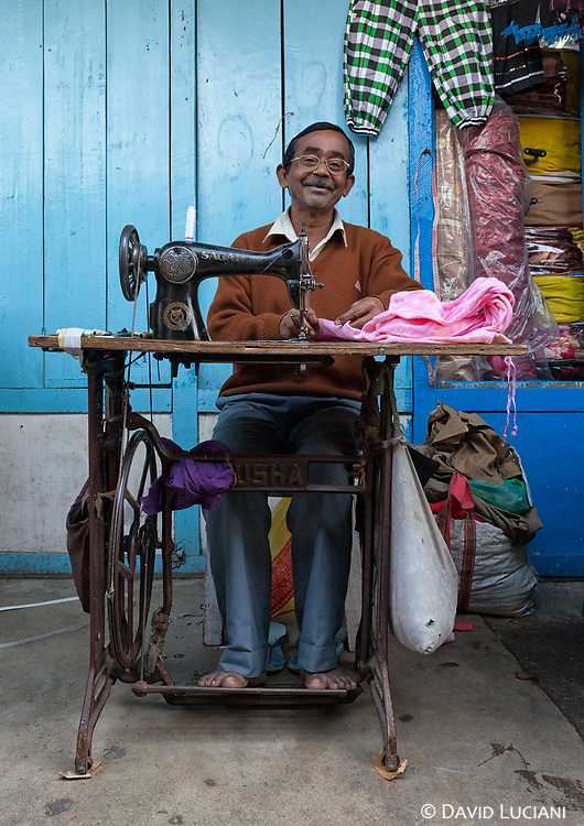 An Indian tailor working on a sewing machine along the market alley of Itanagar.