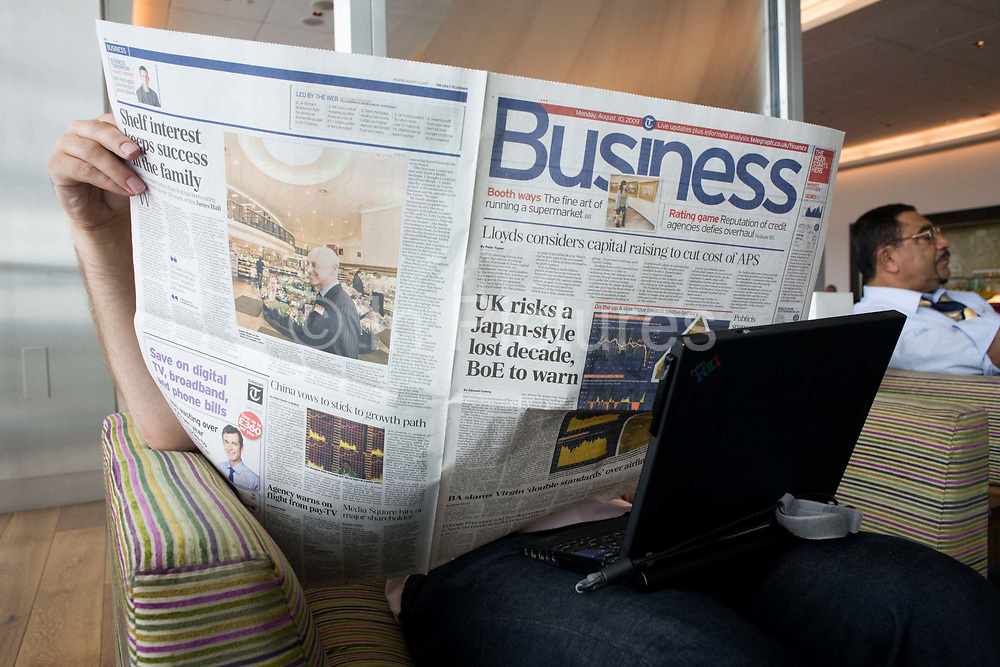 """In the British Airways Galleries First lounge at Heathrow Airport's Terminal 5, an unseen business passenger hides his face while reading the Business section of the Daily Telegraph. With his laptop perched across his knees the anonymous man sits by a window where natural light is a feature of this exclusive facility (only available to passengers travelling in First and Gold Executive Club members) designed by Artwise. The lounge's 15,000 sq ft complex was built at the cost of £60 million. From writer Alain de Botton's book project """"A Week at the Airport: A Heathrow Diary"""" (2009)."""