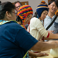 (left-right) Lorandina Sheche, shows, Ai Shinozaki, 30, Ikumi Dohi, 40, and Kazuki Shimizu, 32, demonstrates how to prepare sourdough for the clay oven, during the Zuni Art Walk and Market on Saturday in Zuni Pueblo.