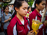 "01 MARCH 2018 - BANGKOK, THAILAND:    Nursing students from the Thai police hospital participate in a procession at Wat Pathum Wanaram in central Bangkok. Many people go to temples to perform merit-making activities on Makha Bucha Day, which marks four important events in Buddhism: 1,250 disciples came to see the Buddha without being summoned, all of them were Arhantas, or Enlightened Ones, and all were ordained by the Buddha himself. The Buddha gave those Arhantas the principles of Buddhism. In Thailand, this teaching has been dubbed the ""Heart of Buddhism.""    PHOTO BY JACK KURTZ"
