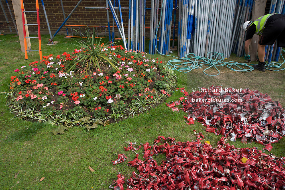 Scaffolding equipment and flower bed during renovation work at a block of flats in the property's garden.