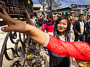 "04 MARCH 2017 - KATHMANDU, NEPAL: Women spin prayer wheels at Swayambhu Stupa in Kathmandu. The temple is also known as the ""monkey temple"" because of the number of macaques that live there.     PHOTO BY JACK KURTZ"