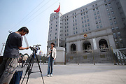 A TV crew from Hong Kong reports from in front of the Beijing court house where the sentencing of Hong Kong reporter Ching Cheong took place August 31, 2006. Ching was sentenced to five years in prison on espionage charges, the latest step in a widening Chinese crackdown on the media and on dissent.
