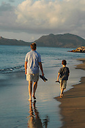 Father and son on a late day beach stroll during a family vacation in Nevis, a Caribbean island in the Lesser Antilles archipelago.