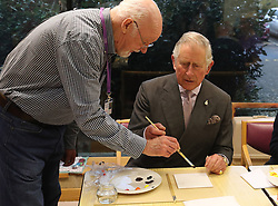 Prince Charles (known as The Duke of Rothesay when in Scotland, centre) standing-volunteer occupational therapist George Bell (left) taking part in a painting class during his visit to the Ayrshire Hospice in Ayr where he met patients and their families, staff and volunteers.