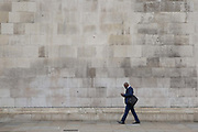 A well dressed businessman walks along Abingdon Street and checks his mobile phone on 10th January 2017 in London, United Kingdom. Abingdon Street is situated in the City of Westminster, an Inner London borough which also holds city status. From the series Our Small World, an observation of our mobile phone obsessions