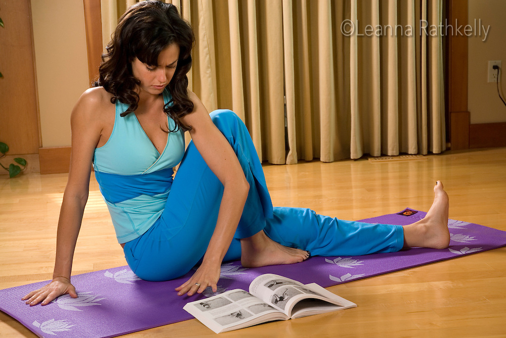 A woman does yoga in her own home.