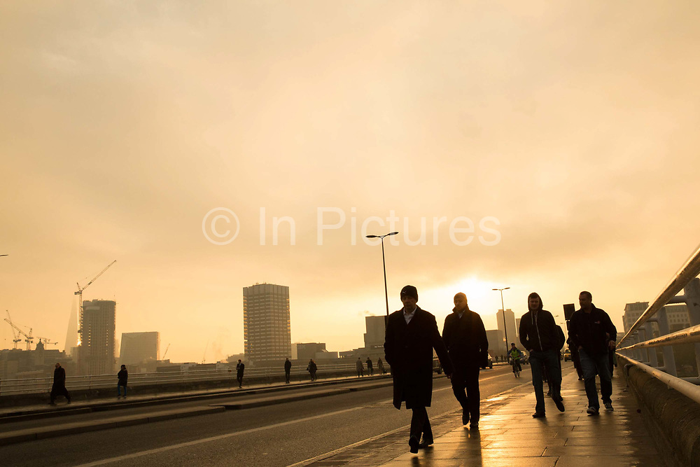 Commuters crossing Waterloo Bridge during a damp morning. The bridge crosses the Thames from Waterloo Station to central London, UK.