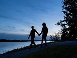 United States, Washington, Bellevue, couple walking along shore of Lake Washington at dusk (silhouette)