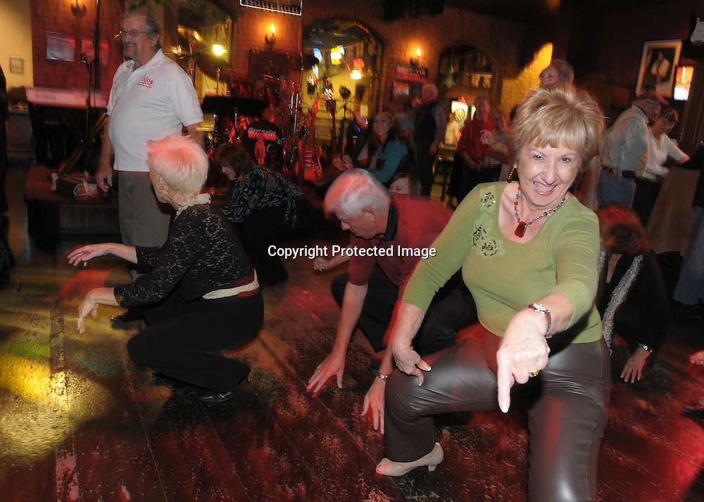 Roselyn Shelley, 68, right, gets down low while doing the Cha Cha Slide while dancing late into the night at the Bourban St. bar in the main downtown square of The Villages, Fla., Saturday, Jan. 17, 2009. (Photo by Phelan M. Ebenhack)