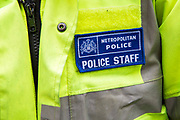 A Police Community Support Officer's (PCSO) badge on the beat in Greater London, UK.