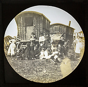 Magic lantern slide portrait of fairground travelling gypsy extended family and caravans, UK circa 1900