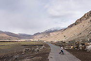 A young nomad girl plays with a soccer ball in the village of Puga on Ladakh's Changtang plateau