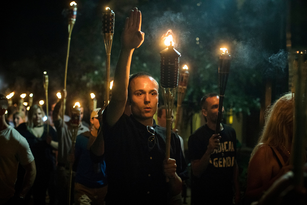"""CHARLOTTESVILLE, VA. USA. August 11th 2017. Members or the Alt-Right led a torch march thru the grounds of the University of Virginia, the night before of the scheduled big rally. <br /> <br /> """"You will not replace us"""" and """"Jews will not replace us"""" were common chants during the march, as a few where giving the Nazi salute.<br /> <br /> The rally occurred amidst the backdrop of controversy generated by the removal of Confederate monuments throughout the country in response to the Charleston church shooting in 2015. The event turned violent after protesters clashed with counter-protesters, which combined with the subsequent vehicle-ramming attack left over 30 injured. (wikipedia)"""