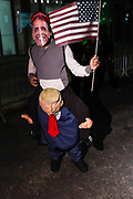 New York, NY - 31 October 2019. the annual Greenwich Village Halloween Parade along Manhattan's 6th Avenue. Donald Trump appears to carry a smiling Barack Obama on his back.