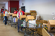 05 NOVEMBER 2013 - PHOENIX, AZ: KENYON CASPER, a volunteer at St. Mary's Food Bank in Phoenix, AZ, packs carts for clients. Demand at St. Mary's has continued to increase even as government assistance is reduced. Over the summer, St. Mary's Phoenix location provided emergency food for 300 - 400 families per day. They are currently supporting about 600 families per day. Part of the increase is seasonal but a large part of it is no clients coming to the food bank for the first time. More than 1.1 million Arizonans who use the Supplemental Nutrition Assistance Program, known as food stamps, saw their benefits reduced Friday, Nov. 1, in a long-planned national cut that was tied to the economic stimulus which was a part of the American Recovery and Reinvestment Act. The cuts imposed last week range from $11 a month for a single recipient to $65 or more for large families. Many of SNAP receipients already use food banks to supplement their government assistance and the cuts in the SNAP program are expected to increase demand even more.   PHOTO BY JACK KURTZ