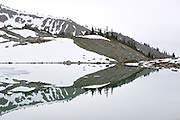 Mountain scenery reflected in perfectly still Blackcomb Lake, on Blackcomb Mountain, near Whistler, British Columbia, Canada.