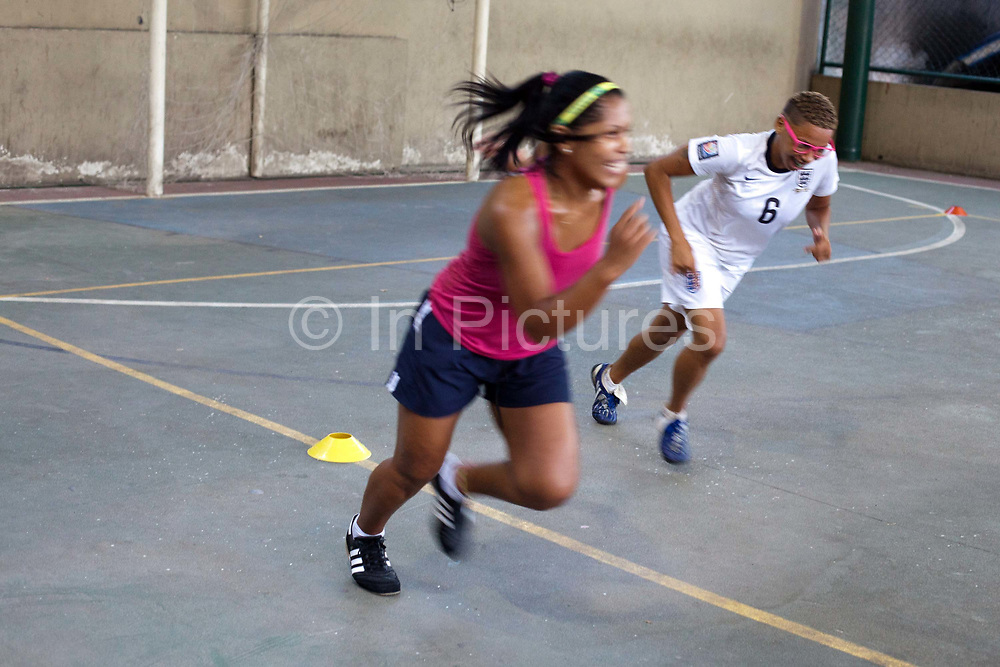 Brazil female Street Child World Cup team (competition winners) training playing football on a concrete pitch in a favela in favela Vila Cruzeiro. Vila Cruzerio is one of the most dangerous favelas in Rio de Janeiro, Brazil. Football classes are run through Dutch NGO Ibiss, giving the local women a chance to be involved in a positive project.